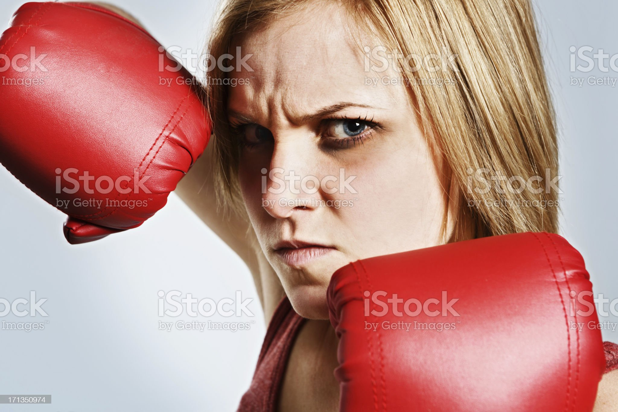 Young blonde female boxer with bruised eye punches angrily royalty-free stock photo