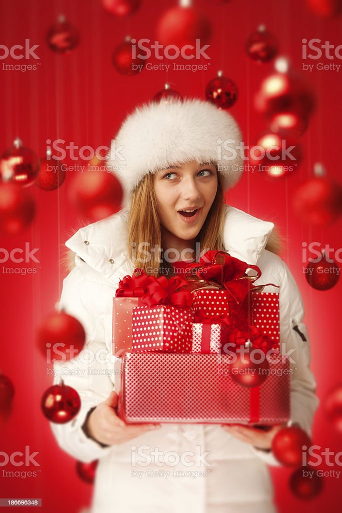 Young Blonde Girl Holding Gifts in Red Christmas Background Vt royalty-free stock photo