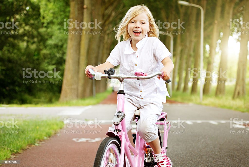 Young blonde girl riding her bike stock photo