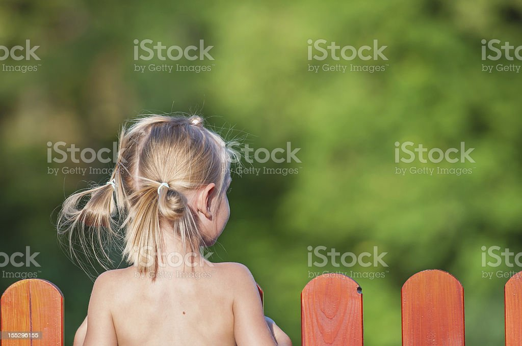 Young Blonde Girl Seen from Behind Looking Over a Red Fence stock photo