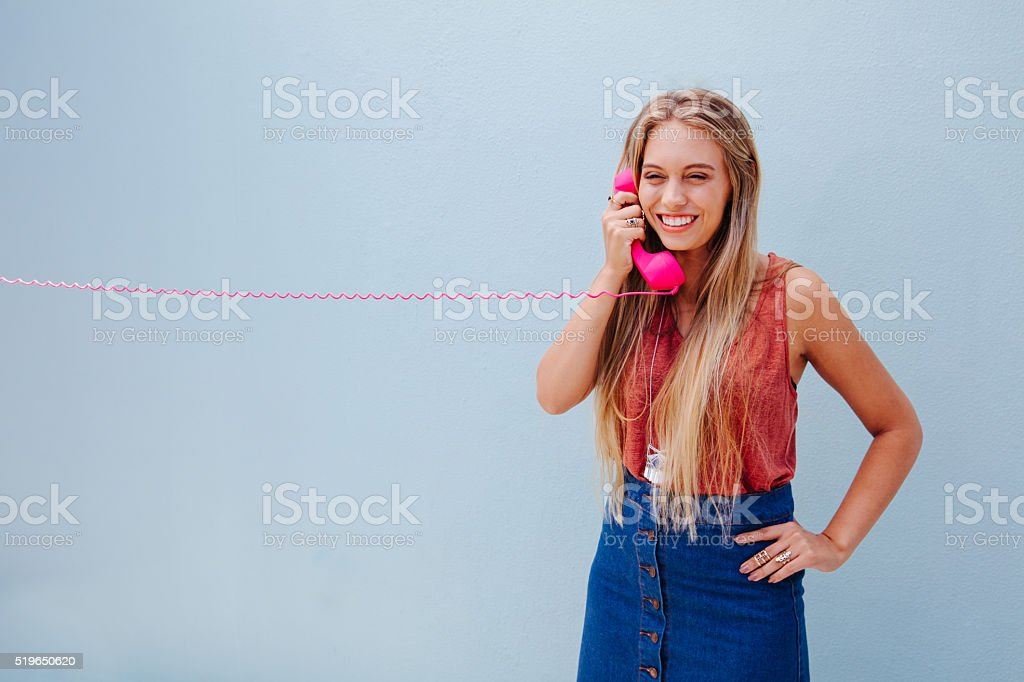 Young blonde girl talking on retro telephone stock photo