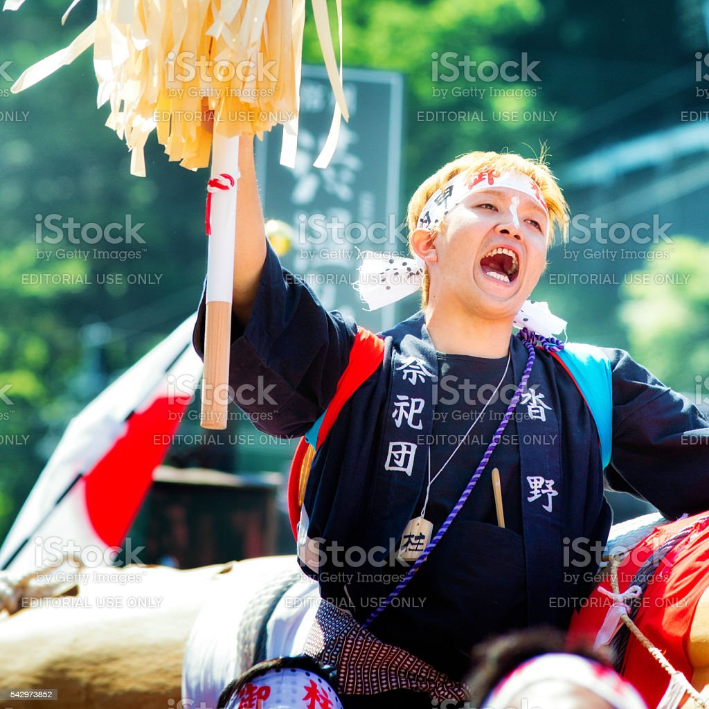 Young blonde Japanese man  hollering during festive procession stock photo
