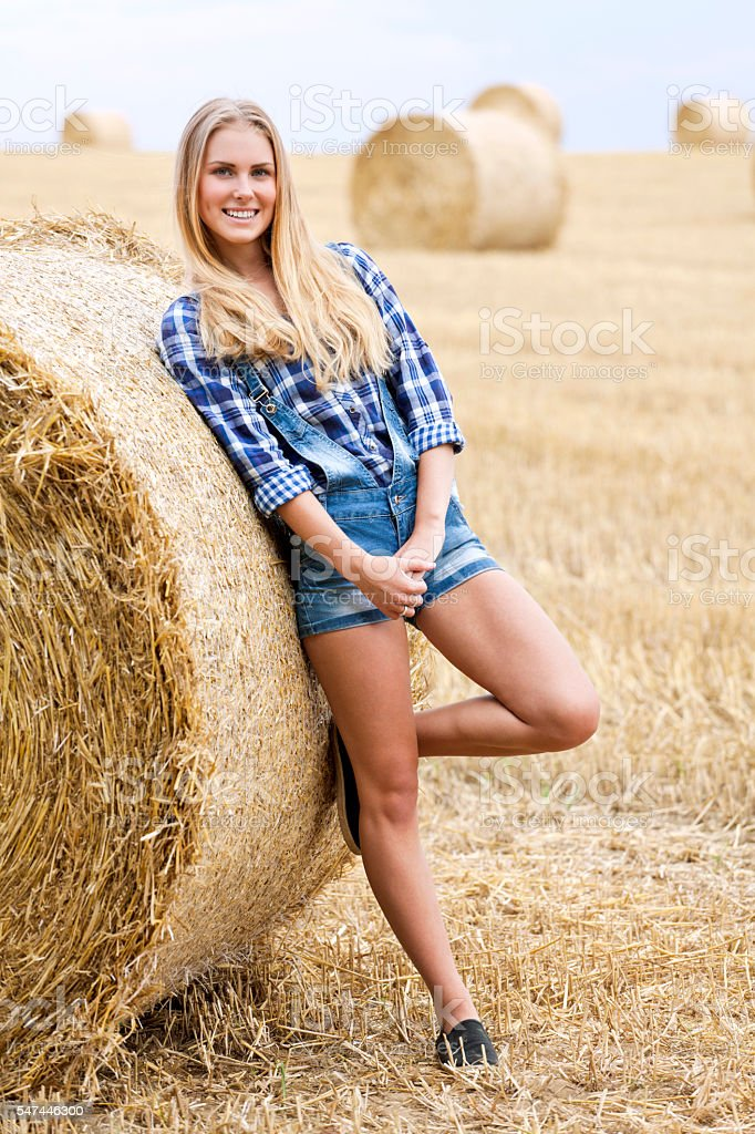 Young blonde leaning on bale of straw on field stock photo