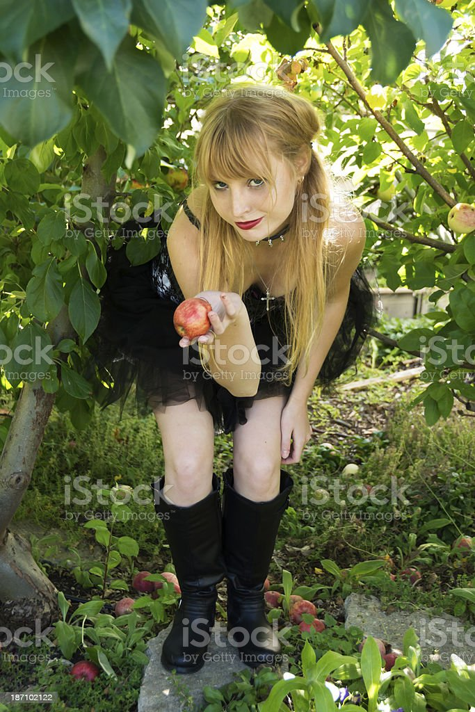 Young blonde leaning over, offering apple. royalty-free stock photo