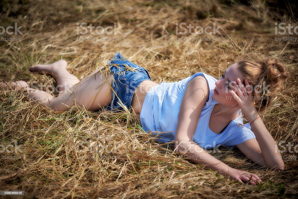 Young blonde lying on a dry straw in the field stock photo