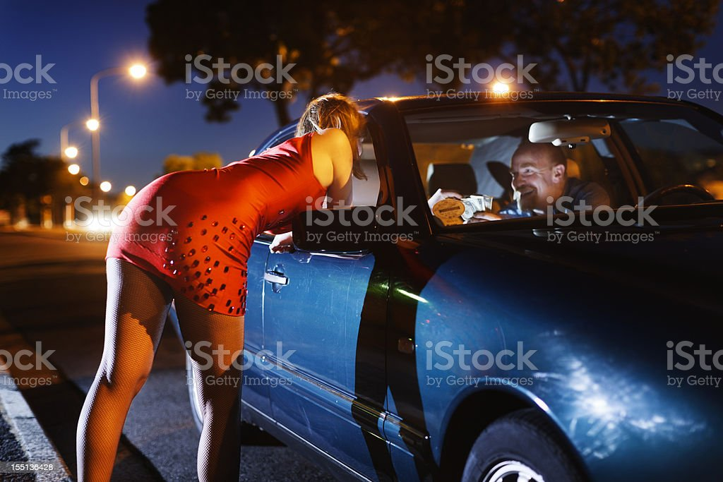 Young blonde prostitute soliciting man in car stock photo