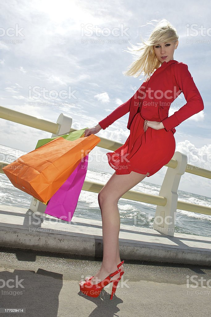 Young blonde shopping woman with bags,sea background royalty-free stock photo