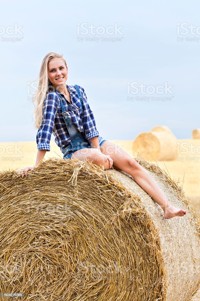 Young blonde sitting on bale of straw on field stock photo