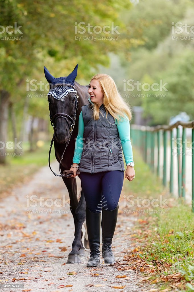 Young blonde woman bringing the black horse back home stock photo