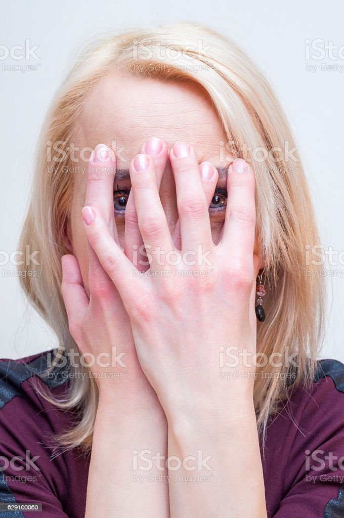 Young blonde woman covering face with palms. Looking through fingers. stock photo