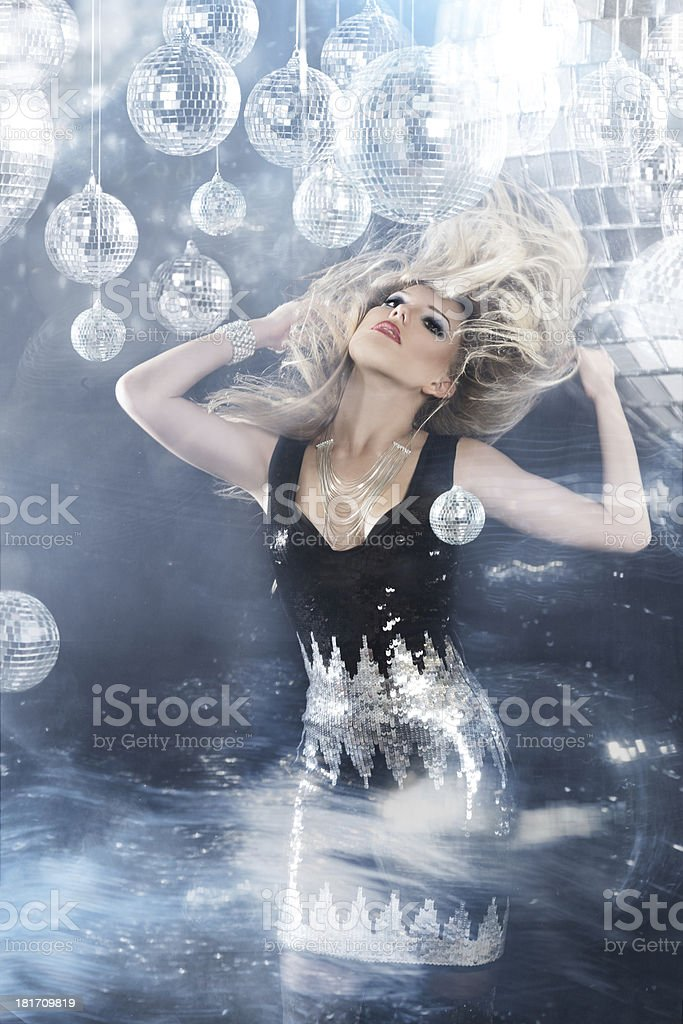 Young blonde woman dancing at night disco club stock photo