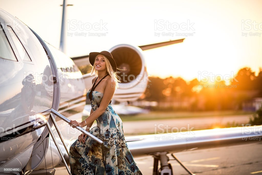 Young blonde woman entering private jet airplane stock photo
