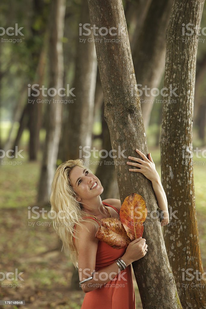 Young blonde woman holding a tree and looking up royalty-free stock photo