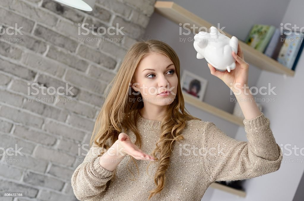 Young blonde woman holding piggy bank upside down. stock photo
