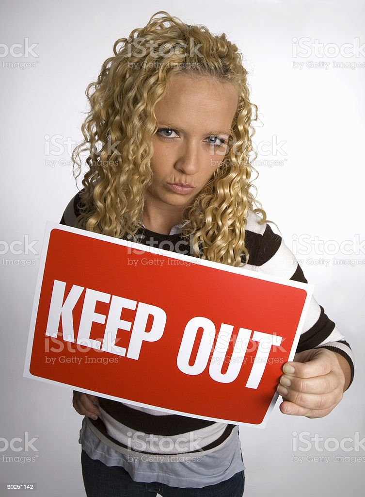 Young blonde woman holds up 'Keep Out' sign royalty-free stock photo