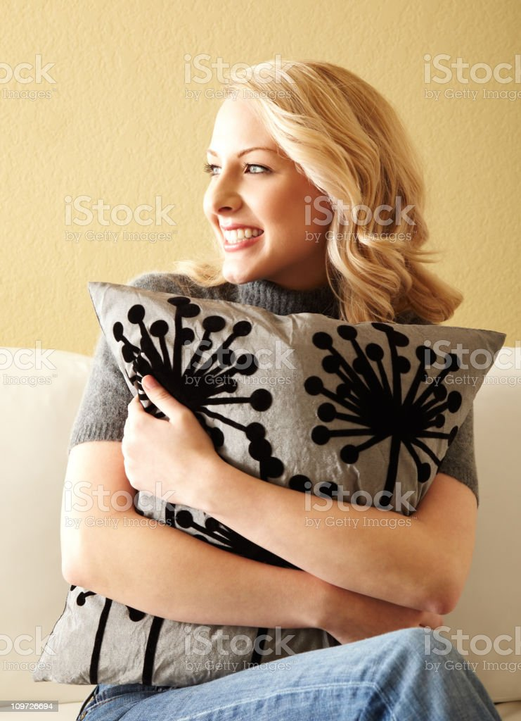 Young Blonde Woman Hugging Pillow and Sitting on Couch royalty-free stock photo