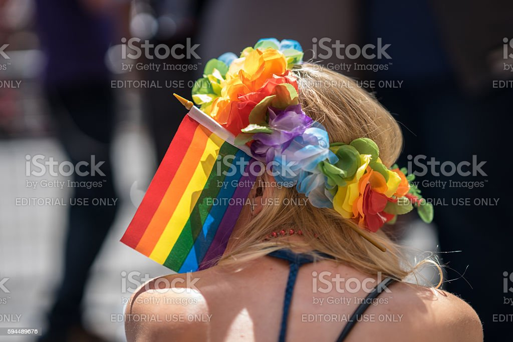 Young blonde woman in a crowd celebrating Pride Parade. stock photo
