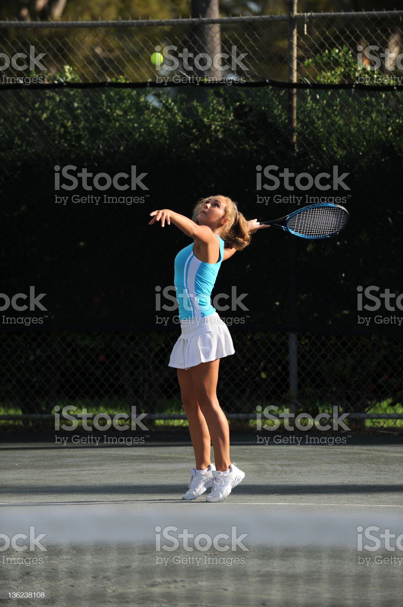 Young Blonde Woman Playing Tennis Serving royalty-free stock photo