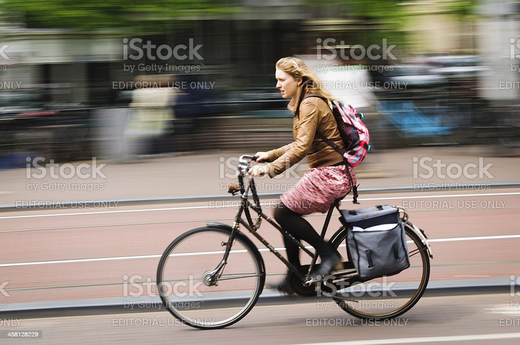 Young blonde woman riding a bicycle in Amsterdam, Holland. royalty-free stock photo