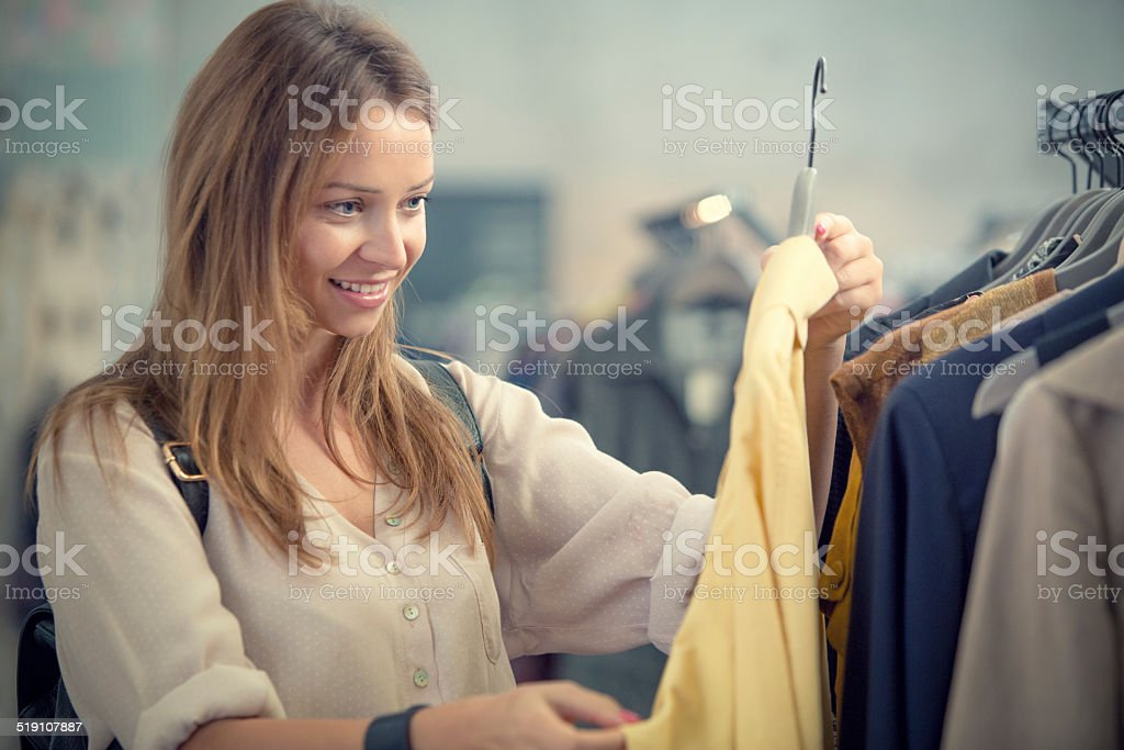 Young blonde woman searching clothes in secondhand clothing shop stock photo