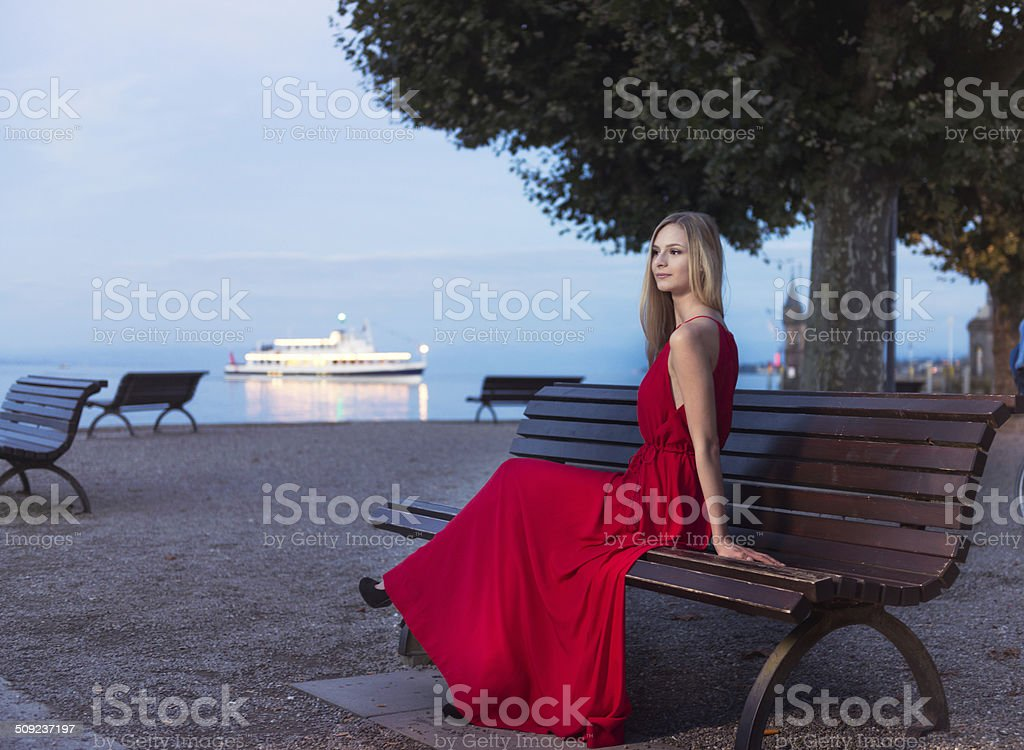 Young blonde woman sitting at sunset on the promenade constance stock photo