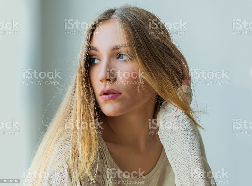 Young blonde woman sitting next to window stock photo
