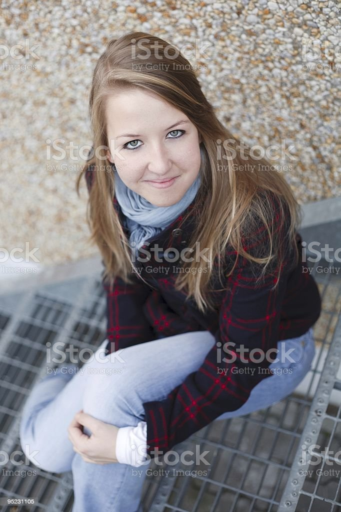 Young blonde woman sitting on steel stairs royalty-free stock photo