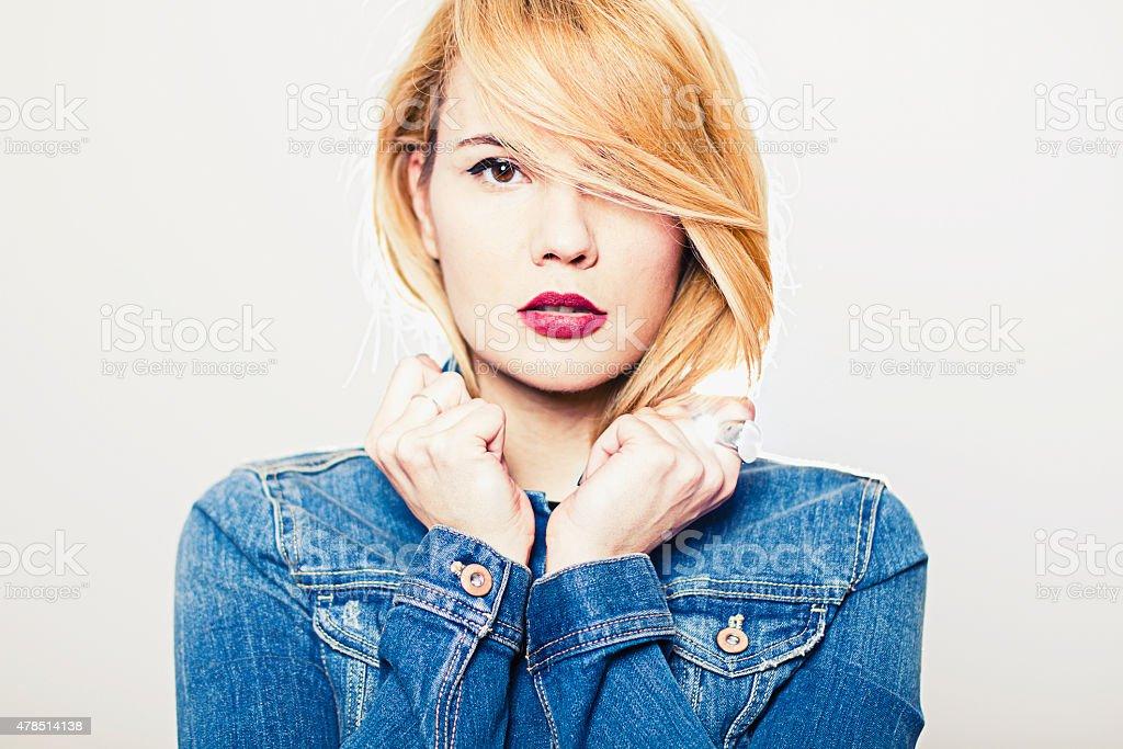 Young blonde woman wearing denim jacket stock photo