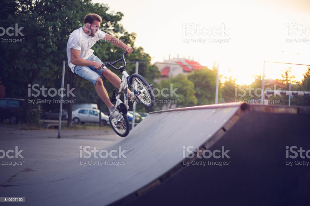 Young BMX bicycle rider on skateboard park