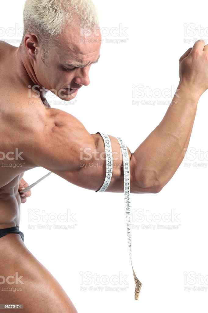 Young bodybuilder measuring his biceps royalty-free stock photo