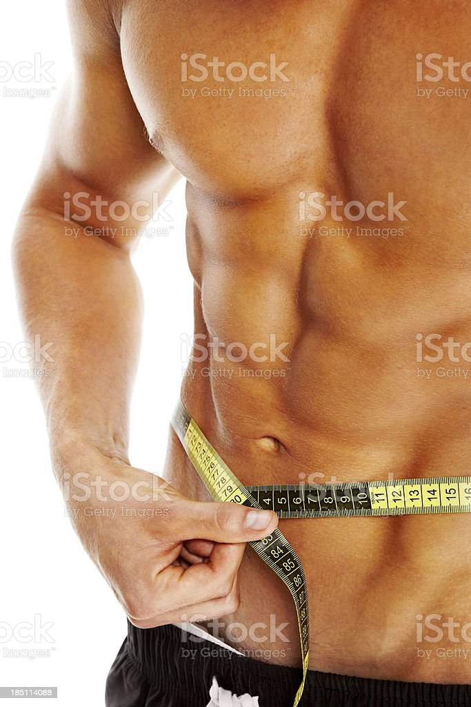 Young bodybuilder measuring his waist royalty-free stock photo