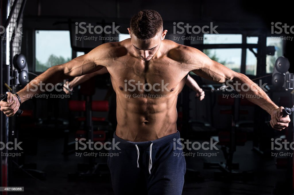 Young bodybuilder using fitness equipment stock photo