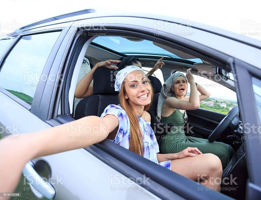 Young boho tourists traveling by car and making selfie stock photo