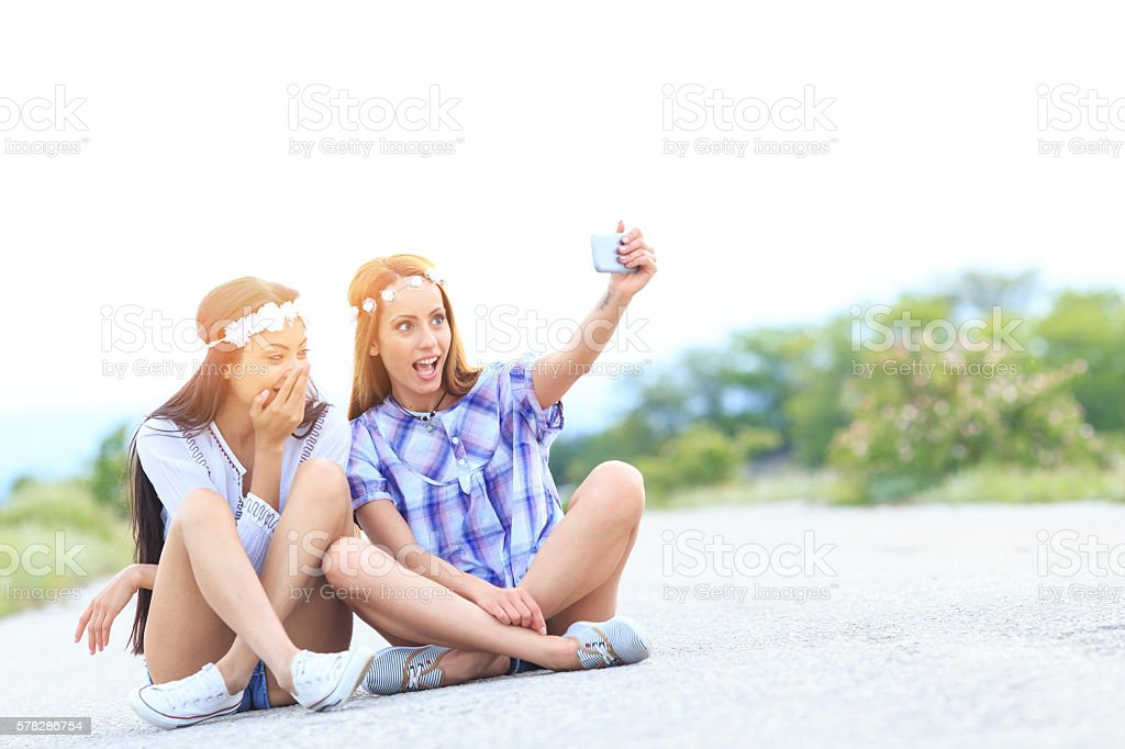 Young boho women sitting on country road and making selfie stock photo