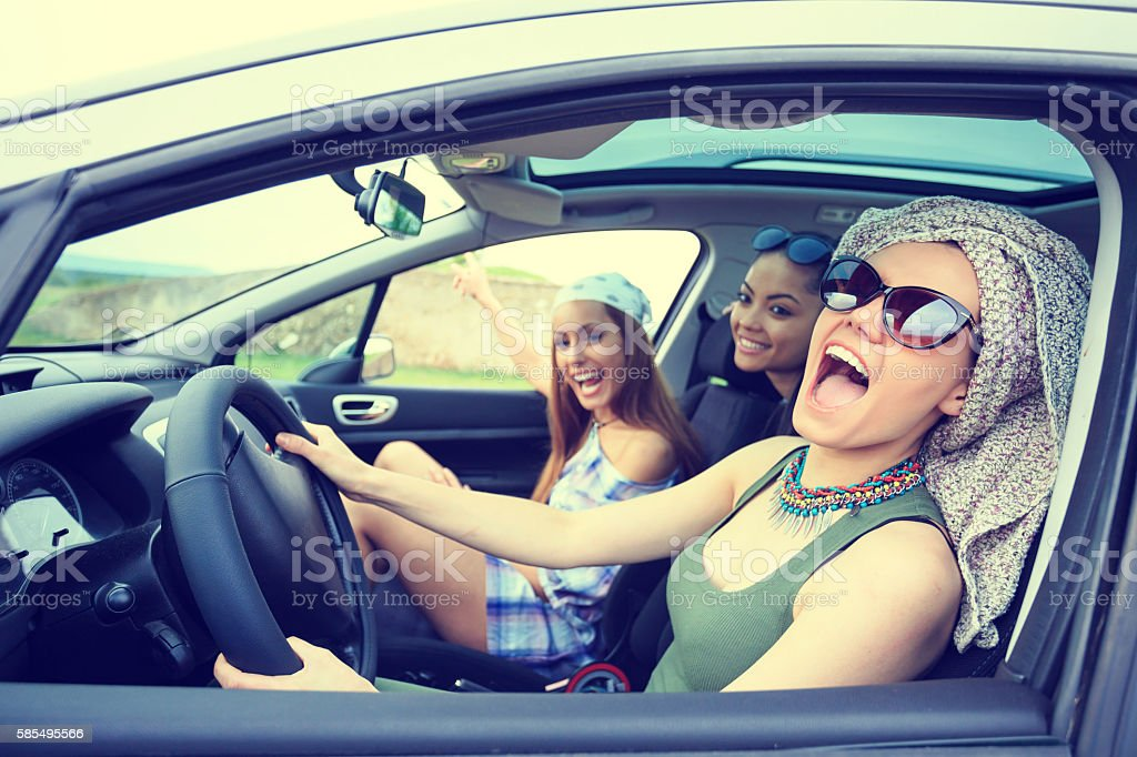 Young boho women traveling and listening music in the car stock photo