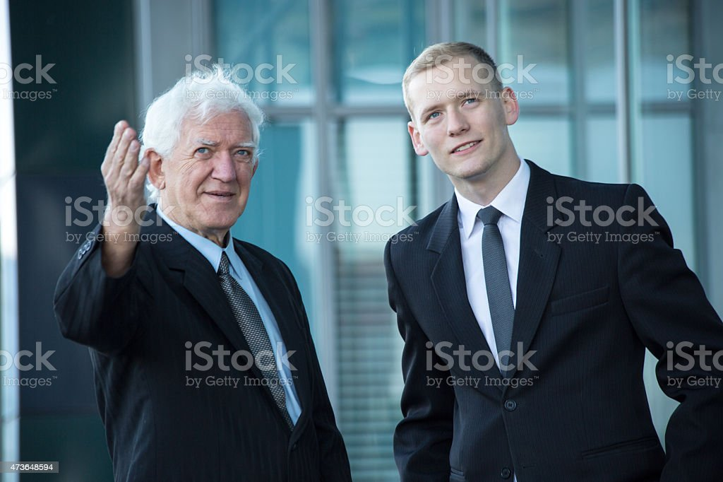 Young boss listening to senior worker stock photo
