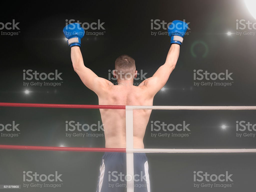 Young boxer with two hands up in the ring stock photo