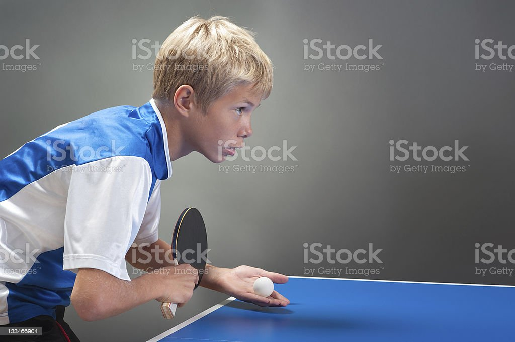 A young boy about to serve in table tennis stock photo