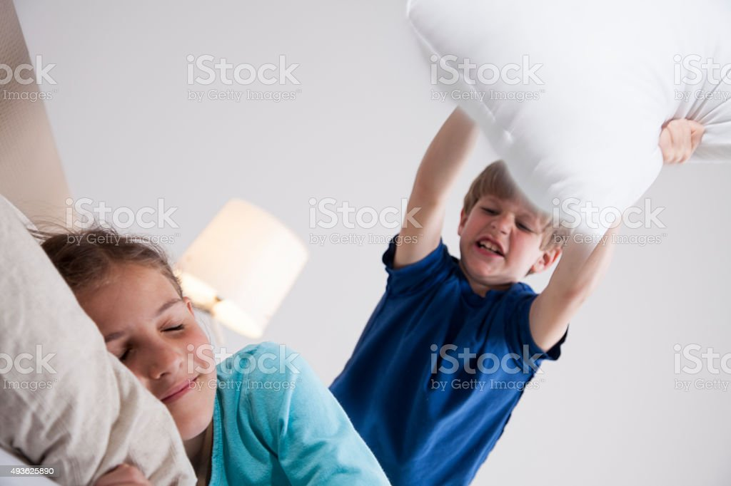 Young boy about to wake his sister with pillow stock photo