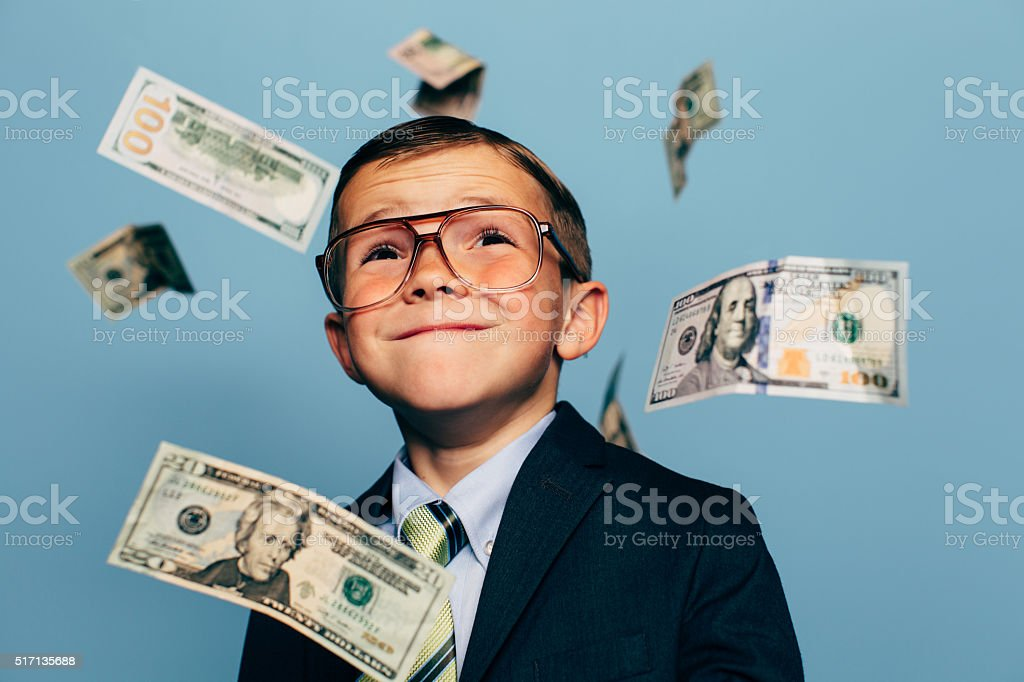 Young Boy Accountant Watches Money Fall from Sky stock photo