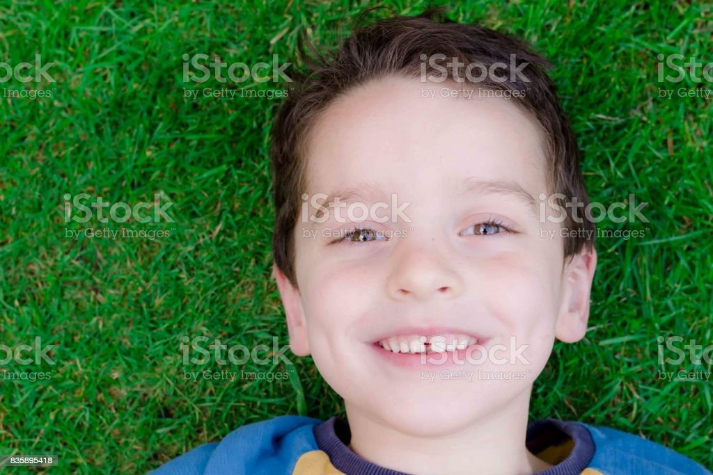 Young boy aged around 5 laying back on grass and smiling stock photo