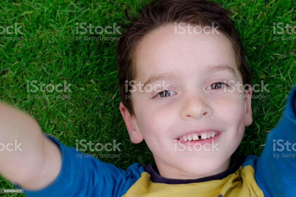 Young boy aged around 5 laying back on grass with arms reaching up stock photo