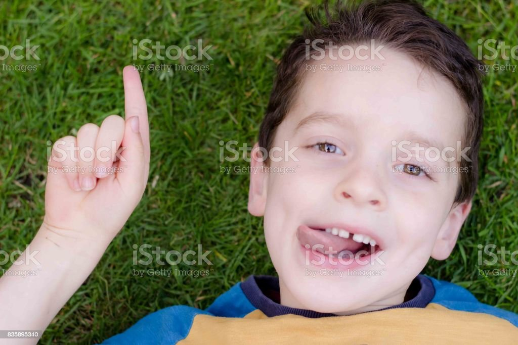 Young boy aged laying back on grass, smiling and pointing stock photo
