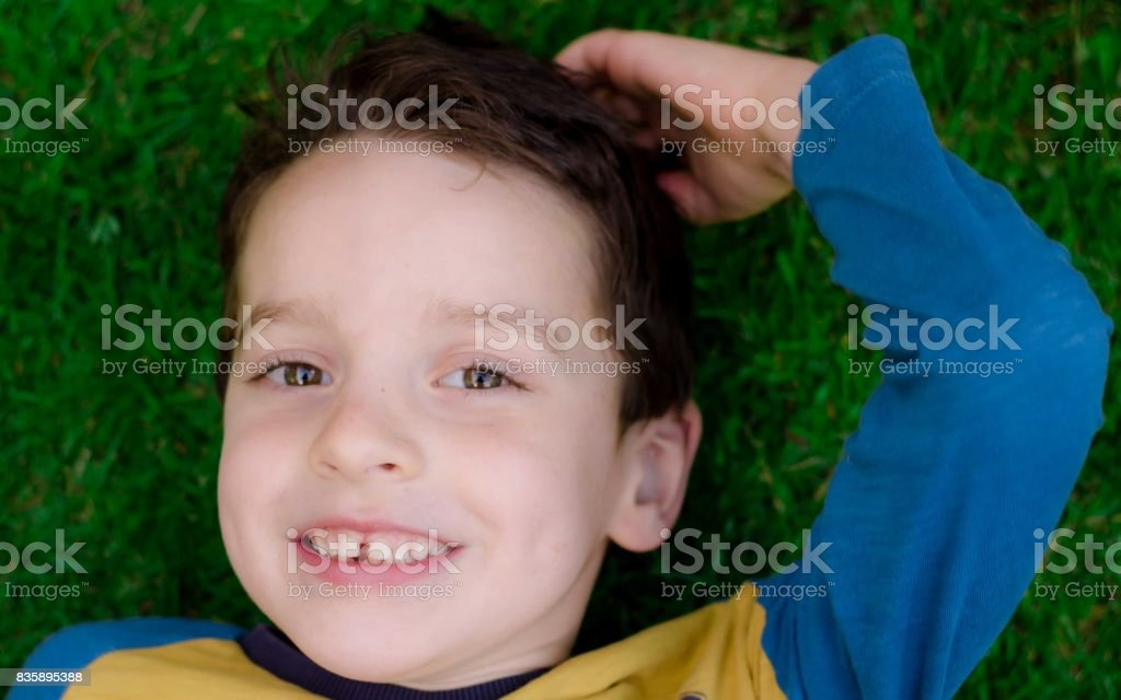 Young boy aged laying back on grass, smiling with hand on head stock photo