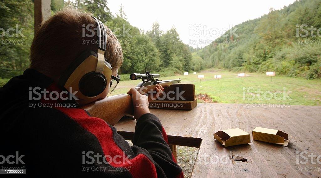 A young boy aiming a gun at a target stock photo