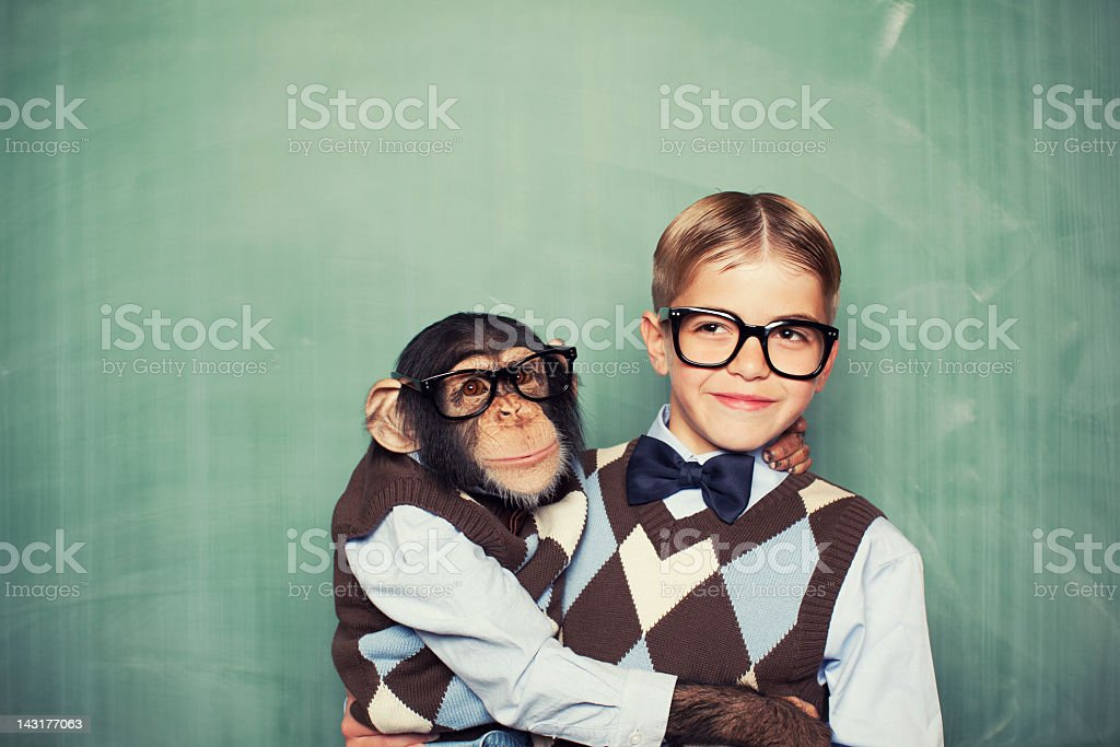Young boy and a monkey dressed alike in classroom stock photo