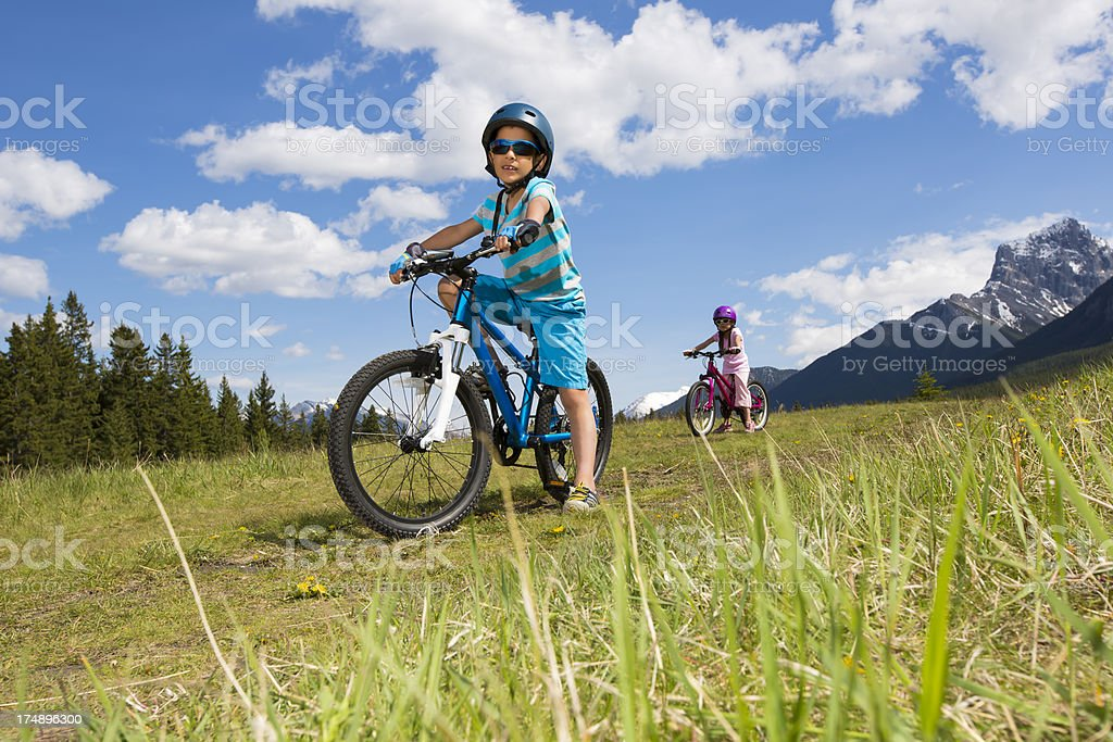 Young boy and girl biking royalty-free stock photo