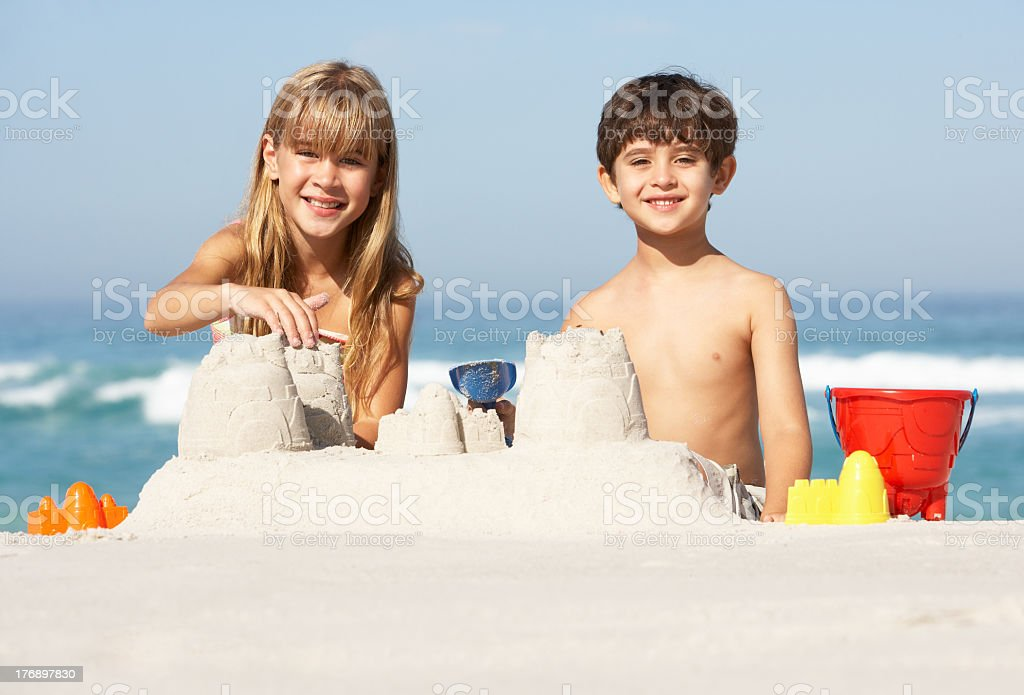 A young boy and girl building a sandcastle on the beach stock photo
