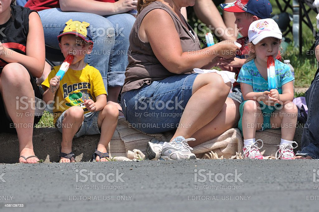 Young Boy and Girl Eating Frozen Treats While Watching Parade royalty-free stock photo