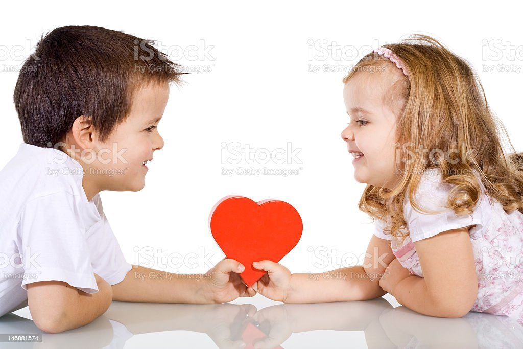 A young boy and girl holding a love heart evenly on a table royalty-free stock photo